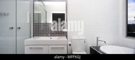 Washbasin set in cupboard unit in modern white bathroom - Stock Photo