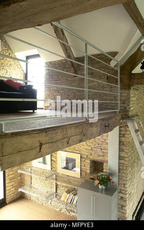 View of the upper and lower levels of a converted stone barn with exposed roof trusses, steel balcony railing, and metal bookshelves. - Stock Photo
