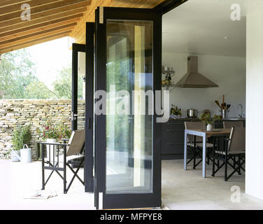 Covered, private patio with open french doors to a tiled, eat-in kitchen. - Stock Photo