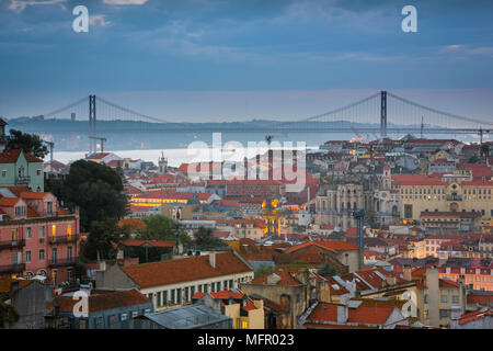 Lisbon dusk, view at dusk across rooftops in the center of Lisbon towards the River Tagus and the Ponte 25 de Abril bridge, Portugal. - Stock Photo
