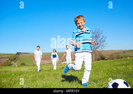 Happy family playing with a ball on nature in spring, summer. - Stock Photo