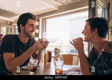 Happy couple eating burger and enjoying in cafe. Young man talking with his girlfriend and smiling while eating at a restaurant. - Stock Photo