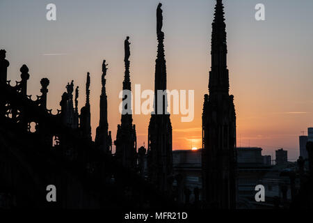 Milan, Italy - 25 April , 2018: The sun sets behind the spires of the Duomo Cathedral, Duomo di Milano. - Stock Photo