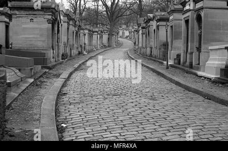 Black and white view of a cobbled alley in the Pere Lachaise graveyard, Paris, France. - Stock Photo