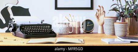 Open notebook and pen placed on a wooden desk with vintage typewriter, fresh plant and pencils in decorative box - Stock Photo