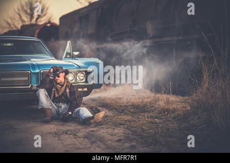 The American Cowboy Story. Caucasian Men Wearing Western Style Clothes and Cowboy Hat, Taking a Moment in Front of His American Classic Muscle Car. Ag - Stock Photo