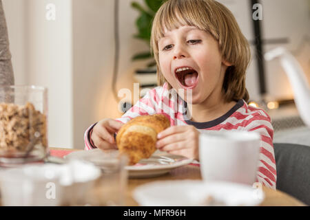 Young boy eating a tasty croissant for breakfast at home - Stock Photo