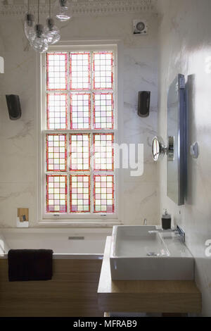 Washbasin on unit next to bathtub beneath window with red stained glass detail - Stock Photo