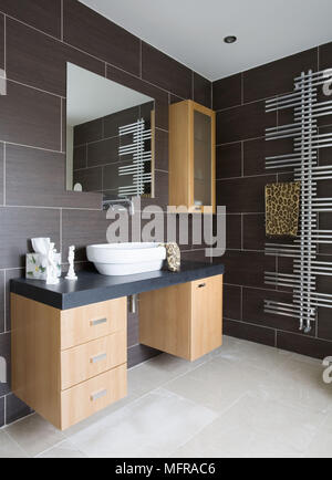 Washbasin set on wall mounted chest of drawers unit in contemporary tiled bathroom - Stock Photo