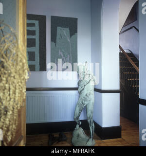 A detail of hallway with a small statue of a boy pictures on the wall wooden flooring and a view of a staircase. - Stock Photo