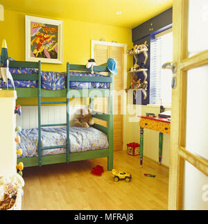 Bunk beds in bright yellow childrens bedroom - Stock Photo