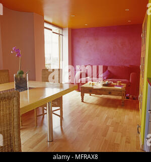 Hot pink sofa and wood dining table in open plan room - Stock Photo