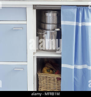 Saucepans and basket of peppers on shelves behind blue curtain - Stock Photo