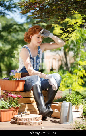 Tired woman in dungarees and wellingtons wiping sweat after gardening work during a hot day