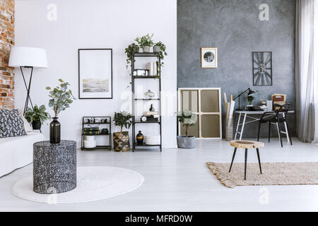 Grey home office with plants, metal coffee table and raw, concrete wall - Stock Photo