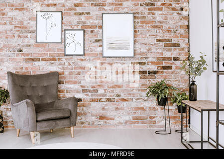 Living room interior with grey armchair, plants and posters on a red brick wall - Stock Photo