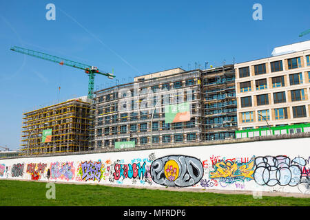 View of original section of Berlin Wall with new office buildings under construction to rear at East Side Gallery in Friedrichshain, Berlin, Germany.  - Stock Photo