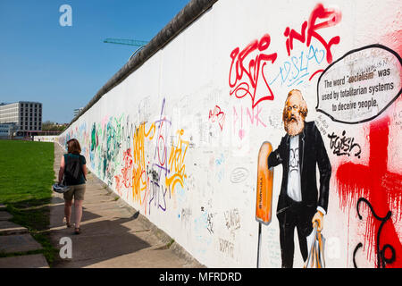 View of original section of Berlin Wall with graffiti at East Side Gallery in Friedrichshain, Berlin, Germany - Stock Photo