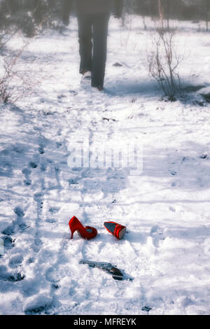 red high heels and a gun in snow, a man is walking away - Stock Photo
