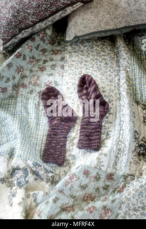 hand knitted socks on a vintage bed - Stock Photo