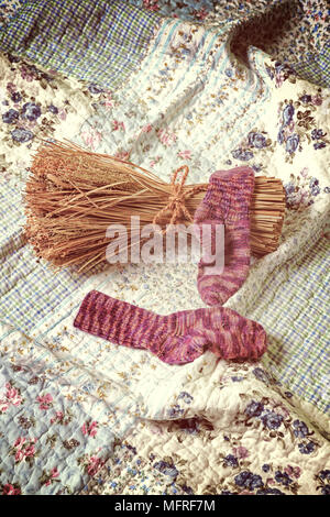 hand knitted socks with a sheaf on a vintage plaid - Stock Photo