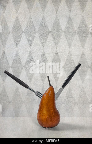 a pear, pierced with a fork and a knife - Stock Photo