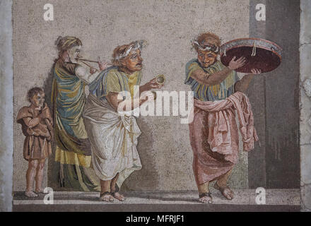 Comedy scene depicted in the Roman mosaic from Villa de Cicero (Villa of Cicero) in Pompeii, now on display in the National Archaeological Museum (Museo Archeologico Nazionale di Napoli) in Naples, Campania, Italy. Street musicians are depicted playing musical instruments often connected with the cult of Cybele: tambourine, small cymbals and double flute (tibia). The mosaic depicts an episode from a comedy, since the figures are wearing theatrical masks. - Stock Photo