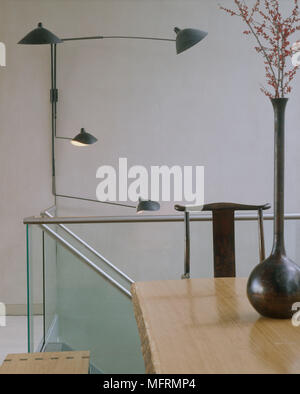 A modern open plan hallway with wooden table on landing area bench seat wall lights tall ceramic vase with twig arrangement - Stock Photo