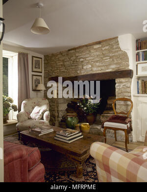 Country cottage sitting room with a wooden coffee table and upholstered armchairs in front of  a stone inglenook fireplace. - Stock Photo