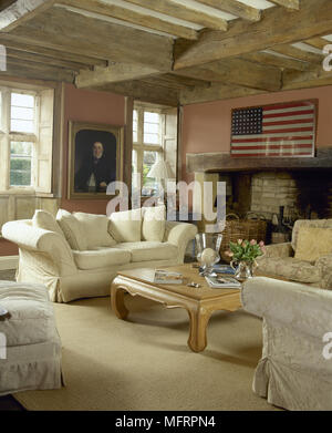 Rustic, country sitting room with wood beamed ceiling, framed American flag, and a comfortable seating area in front of an inglenook fireplace. - Stock Photo