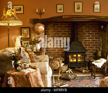 Cosy country sitting room with inglenook fireplace wood burning stove and upholstered armchair. - Stock Photo