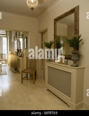 Gilt mirror hanging over radiator cover in neutral open plan hallway. - Stock Photo