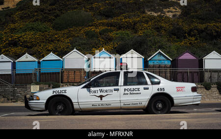 A Fort Worth police car from the USA  parked at Bournemouth beach in England Dorset with beach huts in the background. - Stock Photo