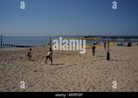 A group takes advantage of a spring heatwave playing volleyball as the temperatures hit 25c on Southbourne beach  Bournemouth England. - Stock Photo