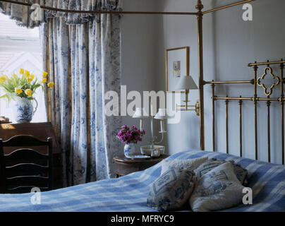 A traditional blue bedroom with brass four poster double bed check bedcover floral open curtains side table wall lights cushions - Stock Photo