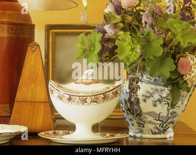 Detail of objects on wooden table including china jug with flowers and metronome. - Stock Photo