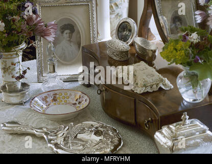 Detail of victorian dressing tabletop with jewellery box antique china and silver with fresh cut flowers. - Stock Photo