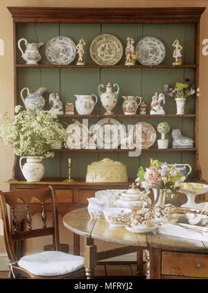 Dining room with round wooden table set for tea in front of green painted dresser and collection of china. - Stock Photo
