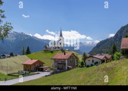 View on a church and some houses in Schmitten on the road from Wiesen to Alvaneu. - Stock Photo
