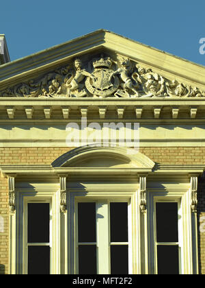 Exterior of a Georgian building with a stone pediment and sculptured coat of arms over the windows. - Stock Photo
