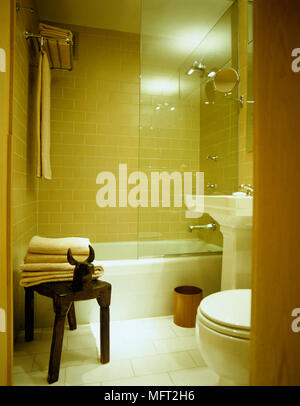 View through open door to compact tiled bathroom with white suite of washbasin bathtub with shower above and toilet - Stock Photo