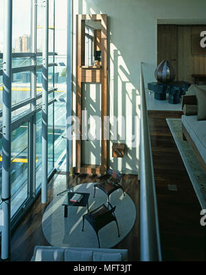 Elevated view of contemporary open plan split level room with sitting area and upper galleried floor - Stock Photo