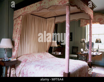 A traditional bedroom with double four poster bed with canopy and curtains, side table, - Stock Photo