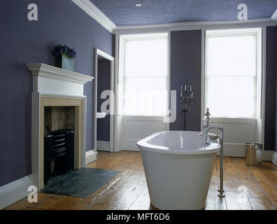 Free standing bathtub in front of fireplace in traditional style bathroom - Stock Photo