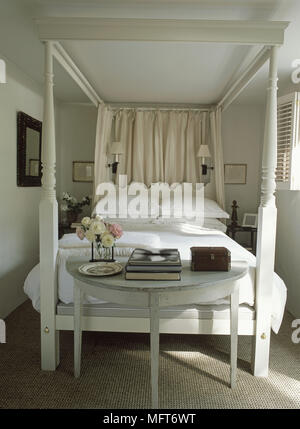 Half moon table at foot of painted four poster bed in country style bedroom - Stock Photo