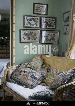 A detail of a traditional green bedroom showing a bamboo cane sofa richly embroidered cushions - Stock Photo