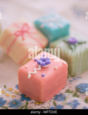 Petit fours in a variety of pastel shades - Stock Photo