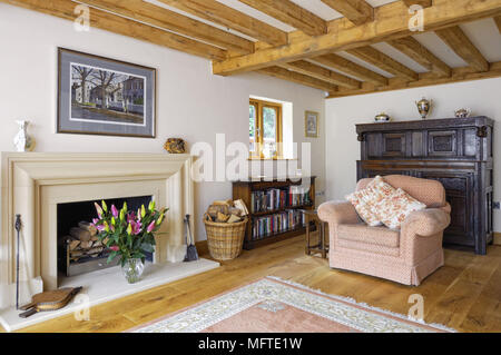 Upholstered armchair next to fireplace in country style sitting room - Stock Photo