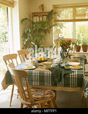 Sunny country dining room with pine table and chairs set for lunch. - Stock Photo