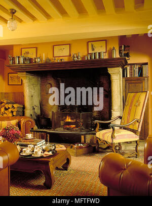 Traditional sitting room yellow walls beamed ceiling lit fire in large pillared fireplace fender mantelshelf  Interiors rooms rustic country fireplace - Stock Photo